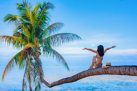 Happy Bikini woman sitting and cheerfully on coconut palm tree over the sea water