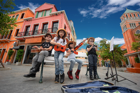 kids playing street musics song on the city walking street for donate, endow, contribute and dole in holidays hobby occasion Stok Fotoğraf - 104816165