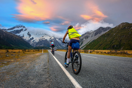 cyclist mountain bikes family enjoy riding on the road in countryside with beautiful mountain cook in New zealand in back ground Imagens