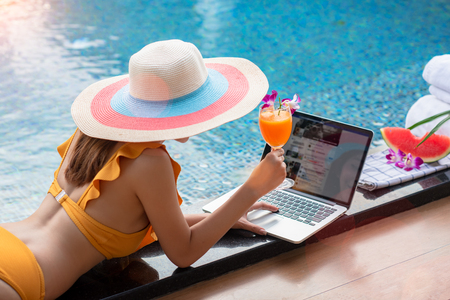 Hand of woman holding orange juice glass while playing social networks on notebook computor at the edge of swimming pool, enjoy relax in summer time vacation