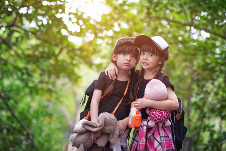 girls travel in field trip together in the rainforest, learning nature for kids experience, wander, stray and worry, bother and fear about straggle lost of the way Foto de archivo