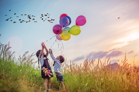 Excited and happy playing kids with balloons running in field meadow with sunset and flock of bird in background Stockfoto