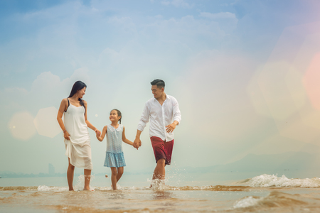 Happy asian family - father, mother, kid hold hands and run together with fun along daylight sea beach. Travel, active lifestyle, parents with children on tropical summer vacations. Stock Photo