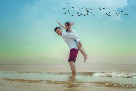 asian parent girl daughter ride upon piggyback of father playing around on the beach, enjoy single father grow up daughter himself without mother beside, flock of bird fly in background