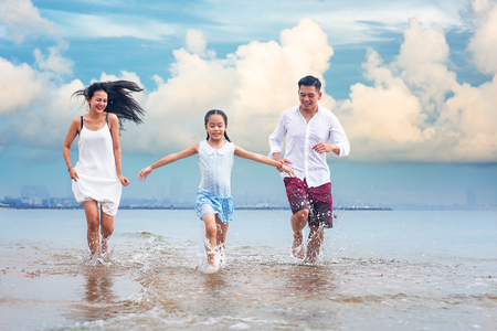 Happy asian family - father, mother, kid hold hands and run together with fun along daylight sea beach. Travel, active lifestyle, parents with children on tropical summer vacations. Фото со стока