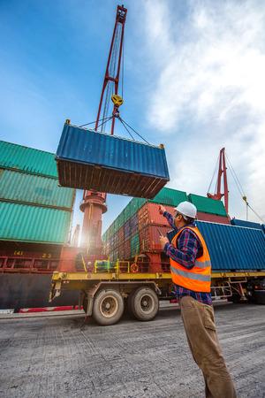 le navire porte-conteneurs d'opération de chargement et de déchargement dans le port prend le contrôle par le manutentionnaire et le contremaître en charge, travaillant dans le terminal portuaire pour les services de logistique et de transport dans le monde entier