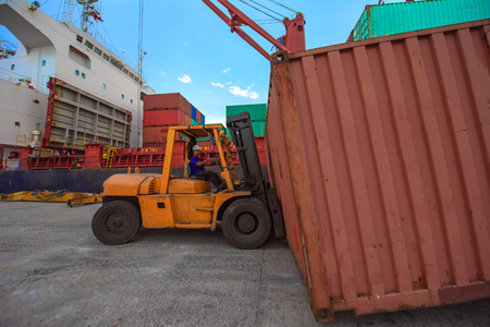 forklift handling unnit of container in port terminal, services from yard delivery to along side the ship for loading, being transhipment export and import Stock Photo