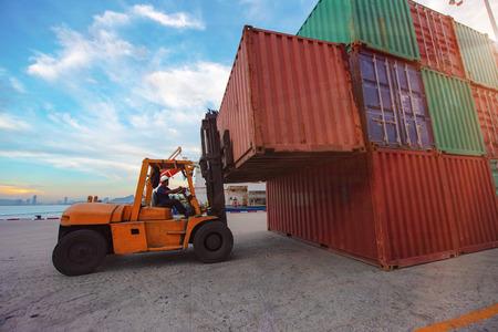 unità container in fase di movimentazione sollevamento con carrello elevatore per il trasferimento dal cantiere alla nave nel terminal portuale Archivio Fotografico