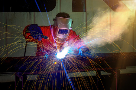 Close up view of professional mask protected welder man in uniform working on the metal sculpture at the table in the industrial fabric workshop