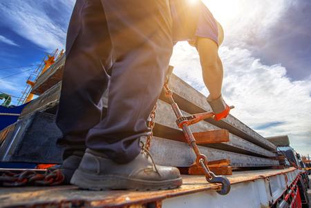 Trabajadores conductor del camión de remolque amarra asegurando la losa de acero en el remolque, amarrando asegurando mercancías apretando la cadena para amarrar antes de la entrega al destino Foto de archivo