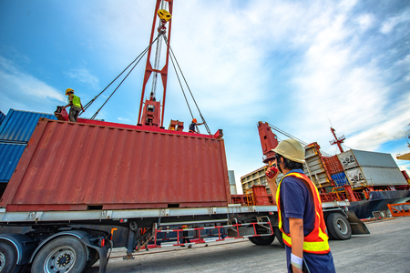 container unit being lifting loading by the ship's crane to accommodate on bay storage on the ship carrier, command by loading master, the services of logistics and transport shipment to worldwide