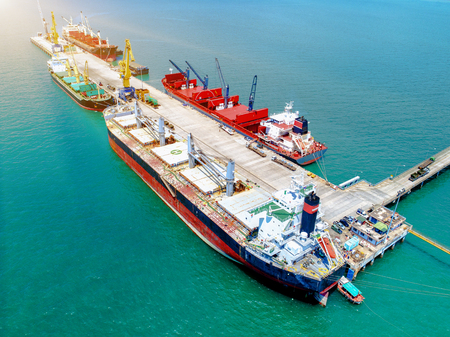 top view, aerial view of sea port terminal keep busy with bulk cargo ships working operation of loading and discharging shipment and cargo transition 免版税图像