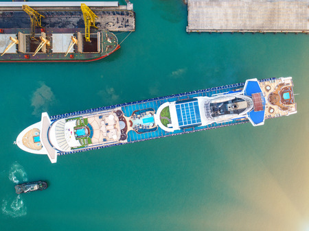 aerial top view of the passenger cruise vessel ship is in the port, arrival and departure of the ship under command and navigation by pilot and captain, withn tug boat assist for safety attending