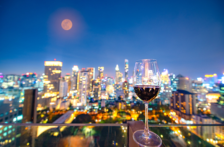 glass of wine standing for celebration at night with the light bokeh of city shining in background Banco de Imagens