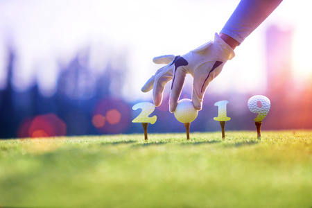 concept of golf ball invitation on incomming year 2019, on the tee off prepare by hand of woman, prepare and ready to hit away the new year success to the fairway, Happy new year and merry chrismas on the golf course Banco de Imagens