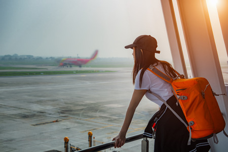 woman traveler passenger delay and lost of flight looking at the aircraft run away in runway with disappointed and upset on missed the flight