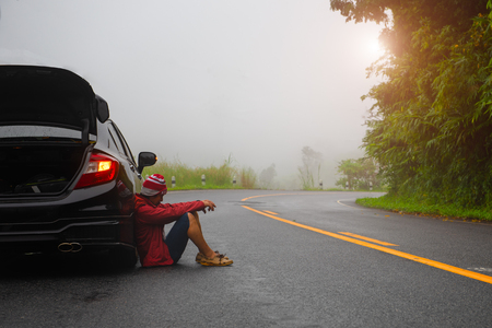 man in trouble on the road of countryside in morning of mist and fog, engine out of order, empty fuel tank of gasoline need help or another assistant of passing car, waiting for anyhelp Stock Photo