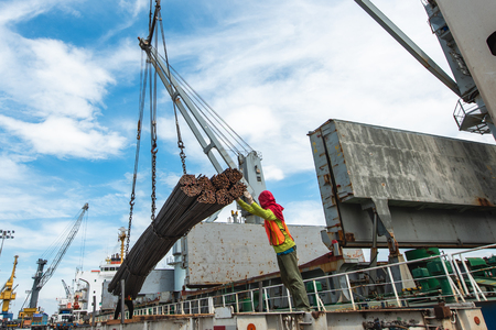 in port harbor working loading and discharging cargo handling by gang of stevedore labor Stock Photo