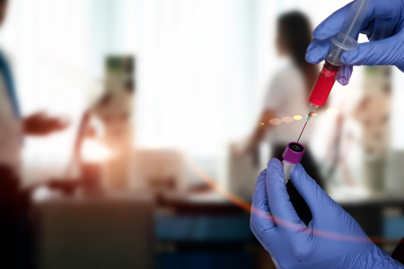 Diagnostician scientist injecting red reactive into tube,  syringe and tubes in hand holding in hand for lab testing resulted Reklamní fotografie