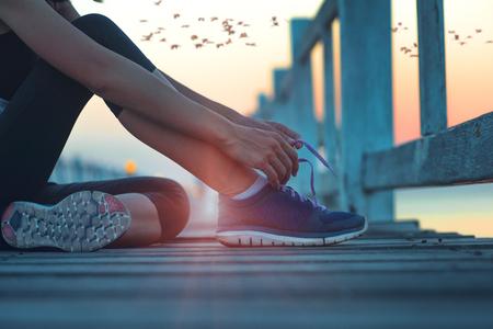 mano de mujer corredor deportivo sentado en el mar puente de madera amarrar zapato después de trotar a lo largo del suset, atar zapato de encaje después de un largo ejercicio