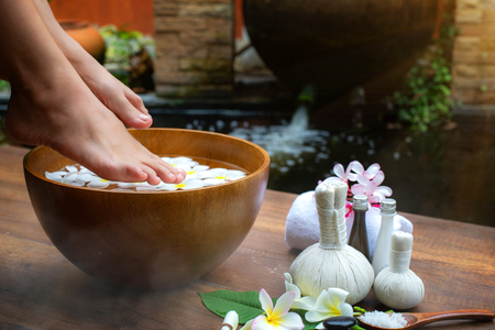 Closeup of leg of a female and feet at spa salon on pedicure procedure. Female legs in water decoration the flowers, relax and feel comfortable zone spa therapy and treatment Stock Photo - 117436352