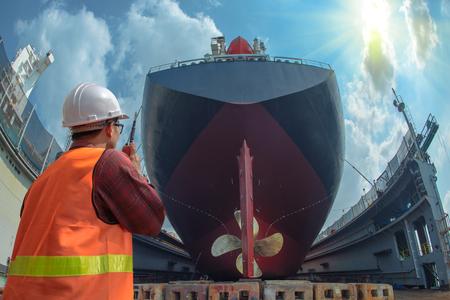 opzichter, voorman, inspecteur, landmeter neemt eindinspectie van de reiniging, reparatie, reconditionering van overromp van het handelsschip in droogdokwerf, klaar om het schip naar zee te brengen Stockfoto