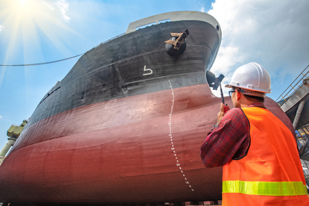 supervisor, foreman, inspector, surveyor takes final inspection of the cleaning, repairing, recondition of over hull of the commercial ship in dry dock yard, ready to delivery the ship to the sea
