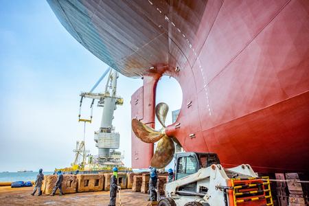 bacino di carenaggio sopra lo scafo della nave commerciale in fase di riparazione, ricondizionamento, verniciatura e pulizia in cantiere navale, fondo di poppa di poppa della nave posato sul supporto della struttura in bacino di carenaggio galleggiante