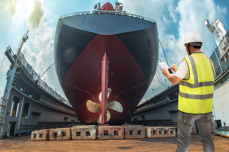 port controller, surveyor, inspector under inspect to recondition, repairing, painting overhaul of the commercial ship, rudder and propeller fixed in properly assemble installation Stock Photo