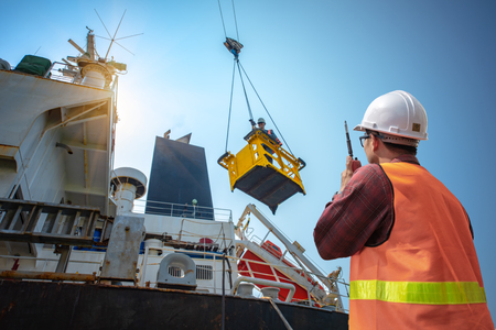 eengineering, loading master connecting with gantry crane driver by walkie talkie for lifting safety in loading the goods or shipment, lifting by gantry crane, working at risk on the high level insurrant