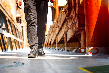 legs of engineering or technician, worker wearing safety shoe walking in mind step on the steel deck plate in walkway at workplace