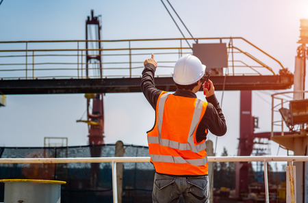 stevedore or foreman or engineering, loading master talks to crane driver by walkie talkie for safety lifting the goods or shipment, lifting by gantry crane, working at risk on the high level insurance 版權商用圖片