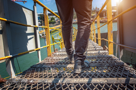 Safety shoe of worker or engineering walking in mind step on the steel checker plate, gangway bridge in safety walkway at workplace, working in high stage and high level of insurance 写真素材 - 118716617