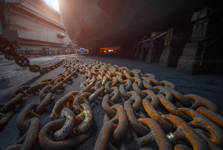 anchor chains bundle laying standing by at bottom layer of the ship in floating dry dock terminal, for recondition maintennant with sand blasting perform