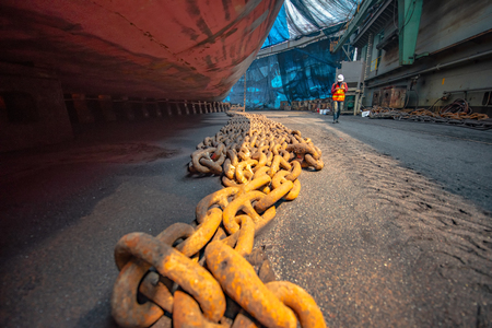 Steel anchor chains caked with rust at an industrial port facility, anchor chains laying on the docking floor for recondition and painting by sand blasting 版權商用圖片