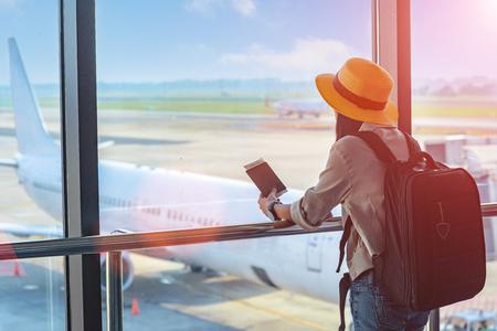 kobieta podróżująca z paszportem oczekująca w strefie tranzytowej lotniska, oczekująca na następny rozkład jazdy, późne opóźnienie odlotu przylotu, brak odprawy na karcie pokładowej