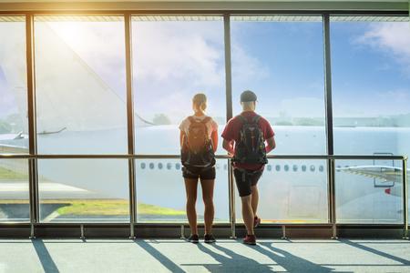Le passager touristique amoureux du couple reste debout dans la salle d'attente pour embarquer dans l'avion pour l'arrivée/le départ, en regardant l'avion entrant et sortant en direct dans le hall Banque d'images