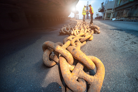 anchor chains bundle laying at bottom layer of the ship in floating dry dock terminal, for recondition maintennance with sand blasting perform, port control and inspector surveying condition in background