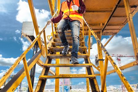 Arbeiter, Ingenieur, der einen Sicherheitsschuh mit Sicherheitsvorschriften trägt, im Auge behält, auf die Stahlgangbrücke am Arbeitsplatz zu gehen, auf hoher Stufe und Versicherungsniveau zu arbeiten