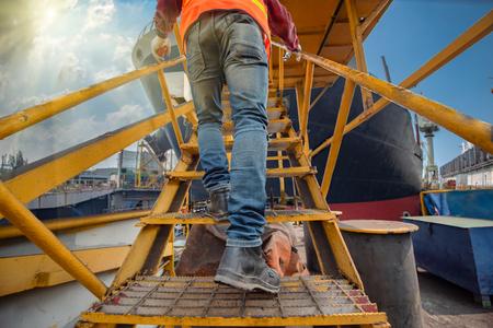 les jambes portant des chaussures de sécurité de l'ingénieur marchent à l'esprit étape vers le poste de travail à un niveau élevé, travaillant à l'étape à un niveau de risque et d'assurance élevé
