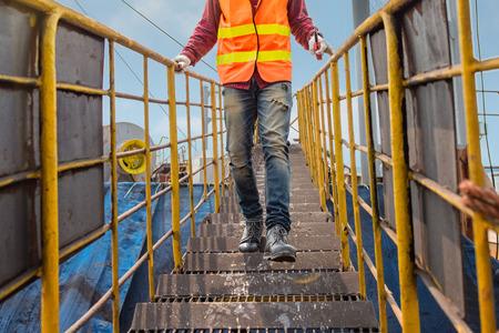 jambes d'ingénieur, technicien, motoriste, ouvrier se dépêchent de courir à l'étage sur une échelle de main courante pour atteindre la destination à temps, travaillant à risque dans un niveau d'assurance élevé