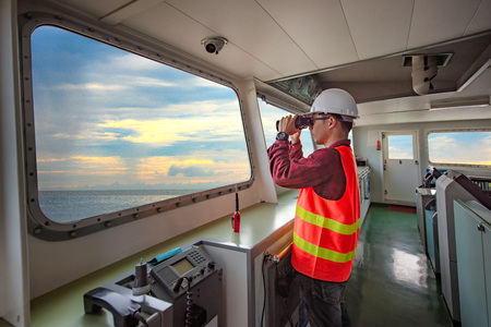 duty officer in charge handle of the ship navigating to the port destination, keep watching navigation on the bridge of the ship vessel under voyage sailing to the sea Stock Photo - 122268867