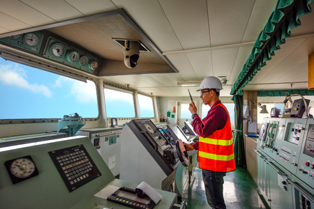 duty officer in charge handle of the ship navigating to the port destination, keep watching navigation on the bridge of the ship vessel under voyage sailing to the sea
