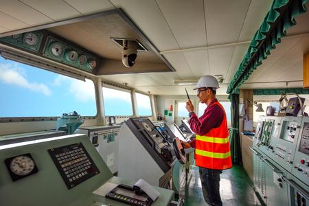 oficial de servicio a cargo manejar el barco navegando hacia el puerto de destino, seguir vigilando la navegación en el puente del barco barco en viaje navegando hacia el mar