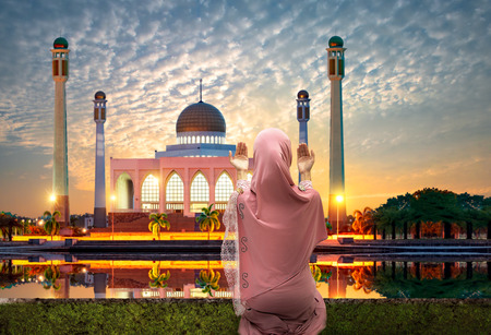 young woman muslim praying in hand in front of mosque at sunset nin back ground, ramadan tradition raising for muslin attractive Stock Photo