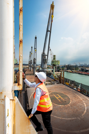 port manager, pilot or engineering foreman, supervisor, master controller in working place, walking in high level at job site, working at risk in work site Stock Photo