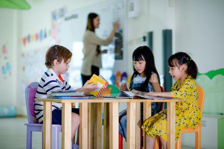 group of international kids in preschool enjoy reading books with teacher watching in background Imagens