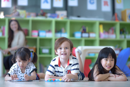 group of international kids in preschool enjoy reading books with teacher watching in back ground