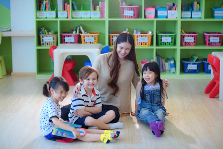teacher and group of international kids preschool attending in class enjoy together 版權商用圖片