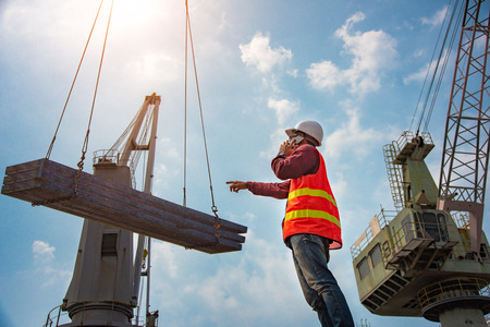 worker, foreman, loading master or engineering works while keep talking on mobile phone online, report swift online speaking on mobile phone, works careless and inattention at risk, high level insurance Stock fotó